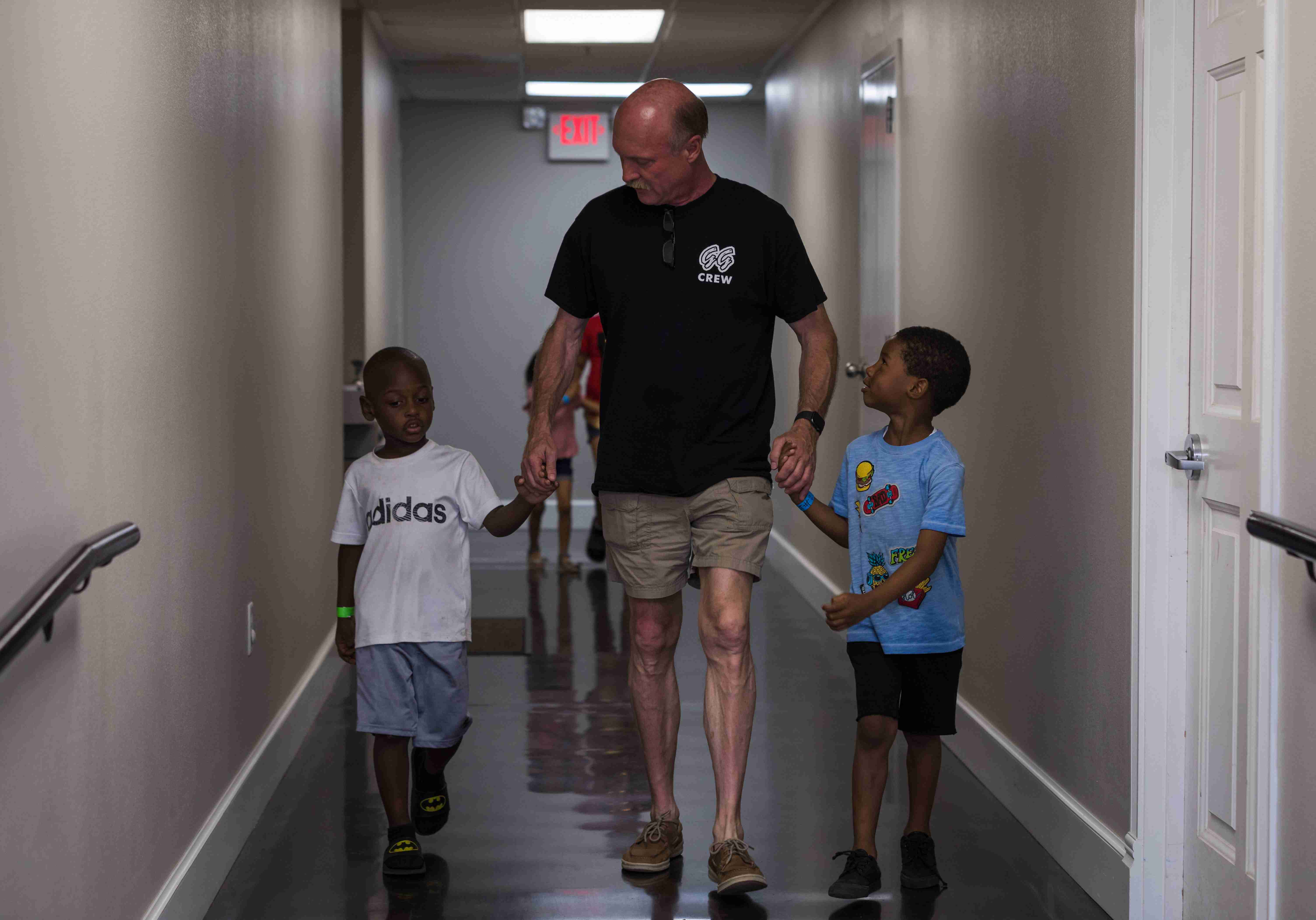 Children Walking with Volunteer Down Hallway